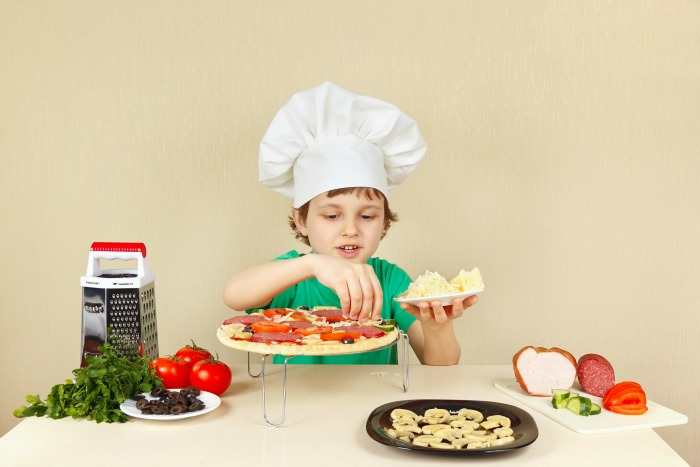 Young smiling boy in chefs hat puts a grated cheese on the pizza crust