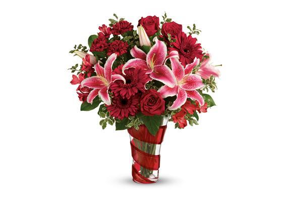 Flower arrangement in red swirl vase with Red roses, hot pink oriental lilies, red gerberas, and red carnations are arranged with pitta negra and lemon leaf flowers