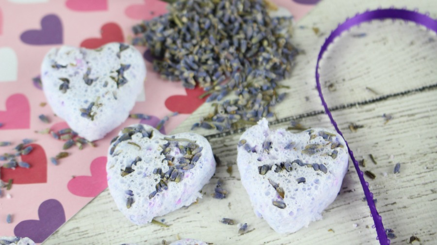 picture of 4 lavender bath bombs with lavender petals on pink heart paper