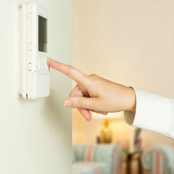 woman's hand turning down thermostat